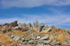 Piatti di pietra in un'erba contro lo sfondo del cielo Immagini Stock
