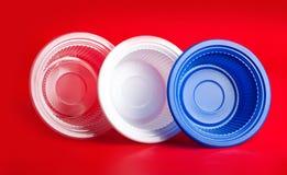 Piatti di plastica colorati su fondo rosso Immagini Stock Libere da Diritti