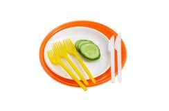Piatti di plastica eliminabili arancio e bianchi, cetriolo, forcelle e Fotografia Stock