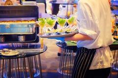 Piatti di trasporto del cameriere con i frutti di mare dell'insalata in vetro su un certo festi Fotografia Stock