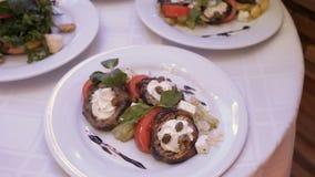 Piatti differenti delle insalate, prodotti a base di carne, formaggio sui piatti su un piatto bianco in un ristorante Giri la mac video d archivio