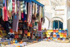 Piatti e abbigliamento decorativi da vendere in EL Souk di Houmt a Djerba, Tunisia immagini stock