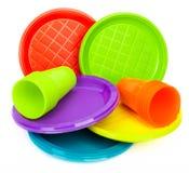Piatti e tazze di plastica luminosi eliminabili su bianco Fotografia Stock Libera da Diritti