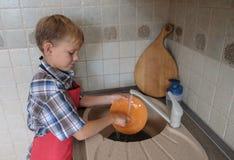 Piatti europei di lavaggio del ragazzo nella cucina fotografie stock libere da diritti