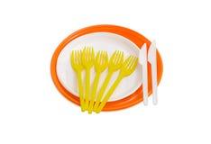 Piatti, forcelle e coltelli di plastica eliminabili arancio e bianchi Fotografia Stock Libera da Diritti