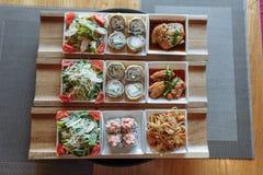 Piatti giapponesi assortiti in piatti quadrati bianchi sui supporti di legno sui precedenti della tavola immagine stock libera da diritti