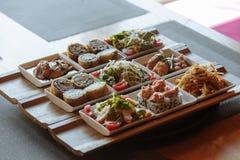 Piatti giapponesi assortiti in piatti quadrati bianchi sui supporti di legno sui precedenti della tavola immagini stock