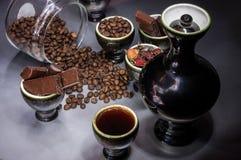 Piatti neri con caffè e grani, pezzi del cioccolato immagini stock