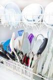 Piatti puliti scintillanti nella lavapiatti Immagini Stock