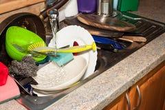 Piatti sporchi nel lavandino dopo le celebrazioni di famiglia Pulizia domestica la cucina Piatti stipati di nel lavandino housewo Immagine Stock Libera da Diritti