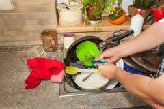 Piatti sporchi nel lavandino dopo le celebrazioni di famiglia Pulizia domestica la cucina Piatti stipati di nel lavandino housewo Fotografie Stock Libere da Diritti