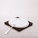 Piatti vuoti, coltelleria, tovaglia sulla tavola bianca fotografia stock libera da diritti