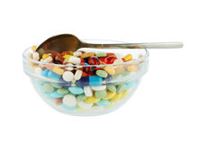Piattino con le pillole ed il cucchiaio many-colored Fotografia Stock Libera da Diritti