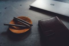 Piattino del caffè, penne di lusso, computer portatile e taccuino sulla tavola concreta fotografia stock libera da diritti