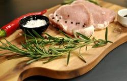 Piatto affettato crudo fresco crudo del raccordo della carne di maiale con i rosmarini, il pepe, il sale, il peperoncino sul bord immagine stock libera da diritti