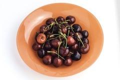 Piatto arancio in pieno delle ciliege rosse dolci Fotografie Stock