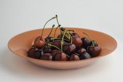 Piatto arancio in pieno delle ciliege rosse dolci Fotografia Stock