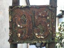 Piatto arrugginito di lerciume del metallo d'annata del quadrato del numero dell'indirizzo stradale con il numero Immagini Stock Libere da Diritti