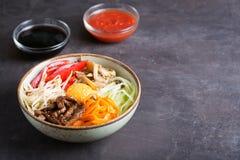 Piatto asiatico tradizionale del Bibimbap con riso e le verdure su fondo scuro con lo spazio della copia fotografie stock