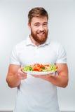 Piatto barbuto allegro felice della tenuta dell'uomo con le verdure fotografia stock libera da diritti