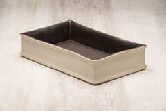 Piatto bianchiccio di cottura con l'interno nero sopra superficie di legno Fotografia Stock Libera da Diritti