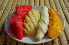 Piatto bianco con frutta affettata: anguria, mango, banana, ananas sulla tavola in un caffè Fotografia Stock Libera da Diritti