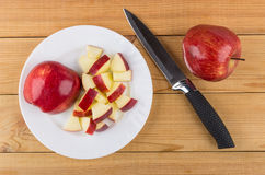 Piatto bianco con i pezzi di mela e di coltello da cucina Fotografia Stock