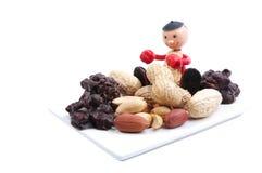 Piatto bianco con i prodotti dell'arachide e poco uomo dell'arachide Fotografia Stock Libera da Diritti