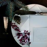 Piatto bianco con il coltello, il ramo dell'abete, il crespino e pezzi di carta d'argento antichi su un fondo di legno Spazio per Fotografia Stock