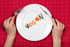 Piatto bianco con il vegano di parola fatto dei pezzi di verdure su rosso Fotografia Stock Libera da Diritti