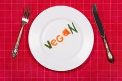 Piatto bianco con il vegano di parola fatto dei pezzi di verdure su rosso Immagini Stock