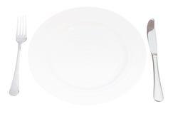 Piatto bianco con l'insieme del coltello e della forcella isolato Immagini Stock