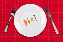 Piatto bianco con la dieta di parola fatta dei pezzi di verdure sul fondo rosso della tovaglia Forcella e coltello vicino  Dispos Immagini Stock Libere da Diritti