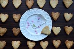 Piatto bianco con la nota ti amo ed i biscotti a forma di del cuore intorno Fotografia Stock