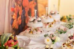 Piatto bianco dei bigné variopinti deliziosi sulla tavola di nozze Fotografia Stock