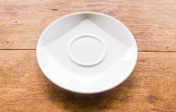 Piatto bianco preso obliquamente disposto su un marrone di legno Fotografia Stock Libera da Diritti