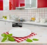Piatto bianco sul placemat della tavola sopra il fondo moderno dell'interno della cucina Immagini Stock Libere da Diritti
