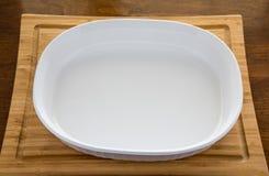 Piatto bianco vuoto della casseruola sul tagliere di legno fotografia stock