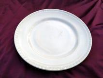Piatto bianco vuoto isolato su un fondo viola immagine stock