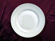 Piatto bianco vuoto isolato su un fondo viola fotografia stock
