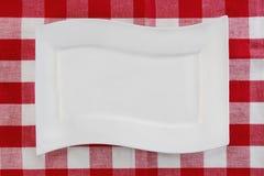 Piatto bianco vuoto sul tovagliolo o sulla tovaglia rosso Vista superiore Modello per il vostro montaggio dell'esposizione del pr fotografia stock