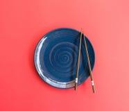 Piatto blu con il fondo di rosa di stile giapponese dei bastoncini immagine stock libera da diritti