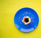 Piatto blu con una certa specie del dessert su fondo giallo immagini stock libere da diritti