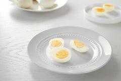Piatto ceramico bianco con la tavola di legno affettata degli uova sode Concetto di nutrizione immagine stock libera da diritti