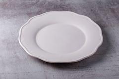 Piatto ceramico bianco dello spazio in bianco vuoto sul bordo del cemento immagine stock libera da diritti