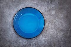 Piatto ceramico blu vuoto su un fondo concreto Vista superiore con Fotografia Stock Libera da Diritti