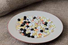 Piatto ceramico con lo scattering delle pillole sul licenziamento homespun grezzo della iuta immagini stock