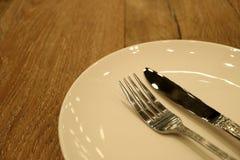 Piatto ceramico del bianco sporco con il coltello da tavola d'argento e forcella sulla Tabella di legno Fotografia Stock