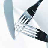 Piatto, coltello e forcelle su una tavola dell'insieme Fotografia Stock