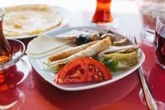 Piatto con alimento vegetariano - panino con gli ortaggi freschi formaggio ed olive accanto a vetro con la bevanda sul caffè ross Fotografie Stock Libere da Diritti